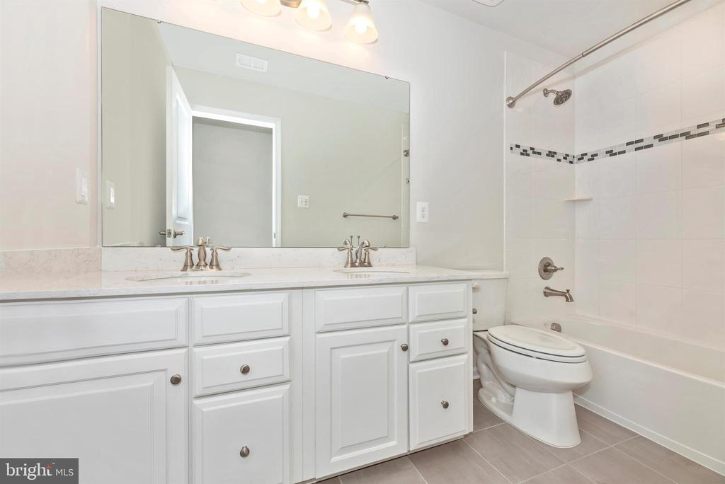 Hall bath with double sinks & decorative tile - 10058 HUTZELL ST, IJAMSVILLE