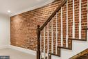 Brick accent wall continues into basement. - 2705 WOODLEY RD NW, WASHINGTON