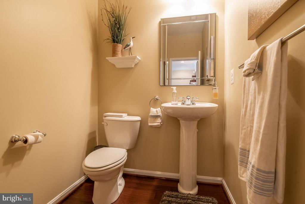 Main level powder room with hardwood flooring. - 19441 COPPERMINE SQ, LEESBURG