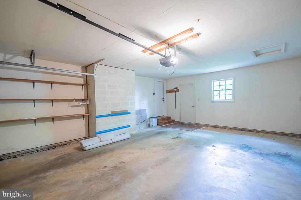 Two-car garage features shelving, rear yard access - 505 WOODSHIRE LN, HERNDON