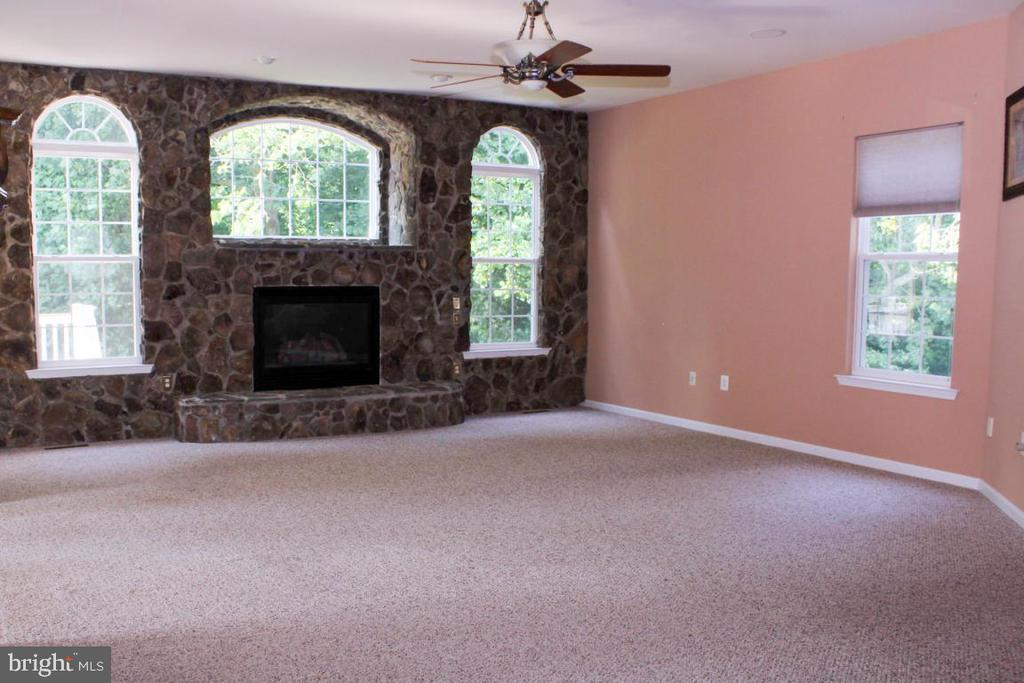 family room with full stone wall - 3220 LACROSSE CT, DUNKIRK
