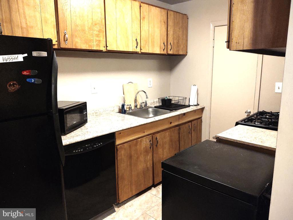 Kitchen with updated appliances and pantry. - 7615 FONTAINEBLEAU DR #2124, NEW CARROLLTON
