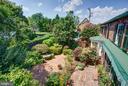 Overlook the lush garden from the Charleston porch - 317 S SAINT ASAPH ST, ALEXANDRIA