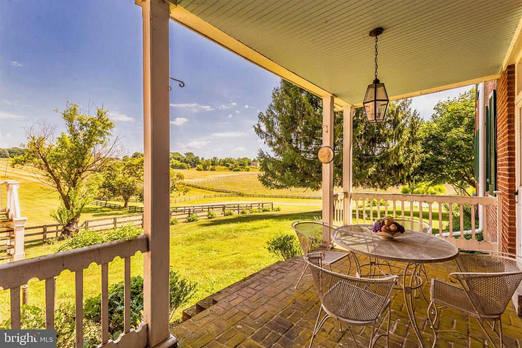 Side porch view overlooking the rolling paddocks. - 7030 DRUMMINE RD, MOUNT AIRY