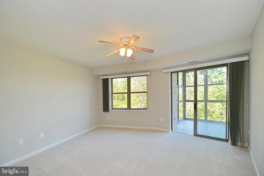 Master bedroom w/sliding glass doors to porch - 19350 MAGNOLIA GROVE SQ #211, LEESBURG