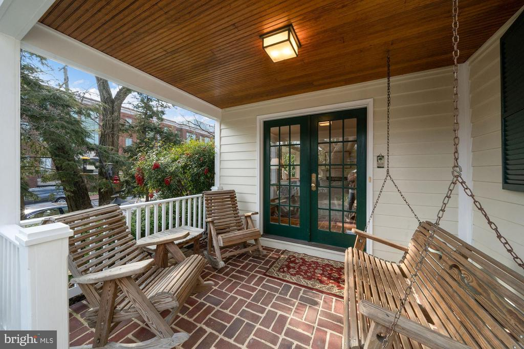 A lovely, covered brick porch with a wooden swing - 639 S SAINT ASAPH ST, ALEXANDRIA