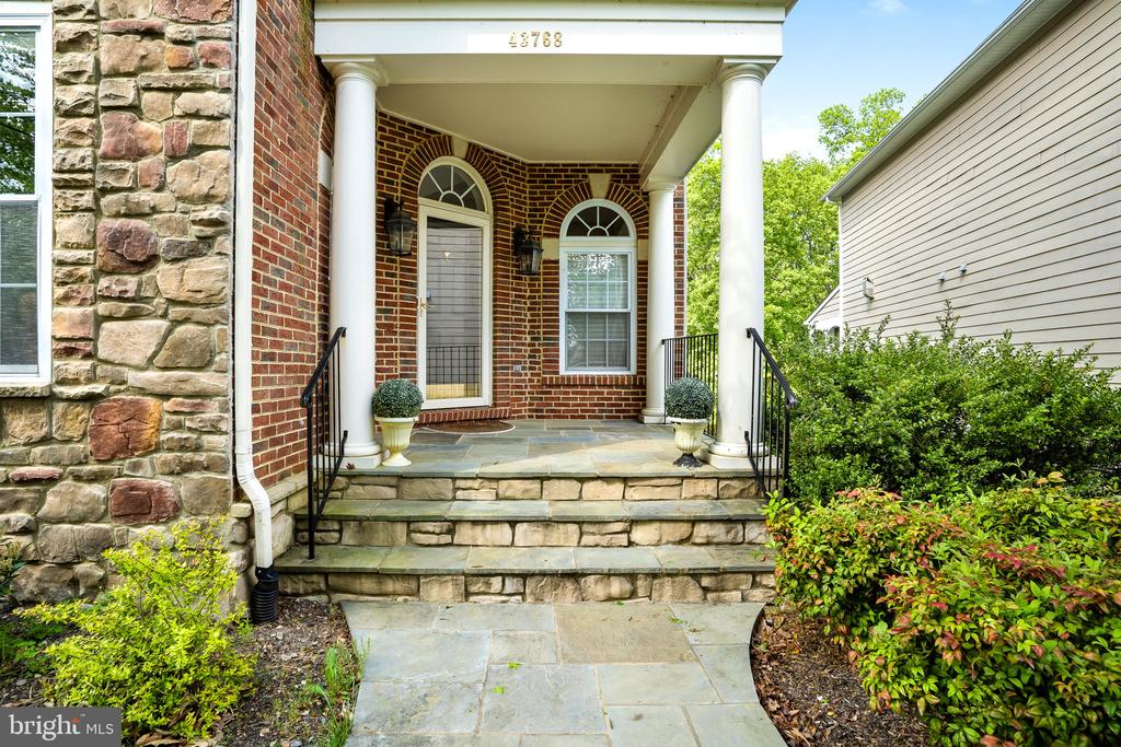 Front entry features a stone walkway and porch - 43768 RIVERPOINT DR, LEESBURG