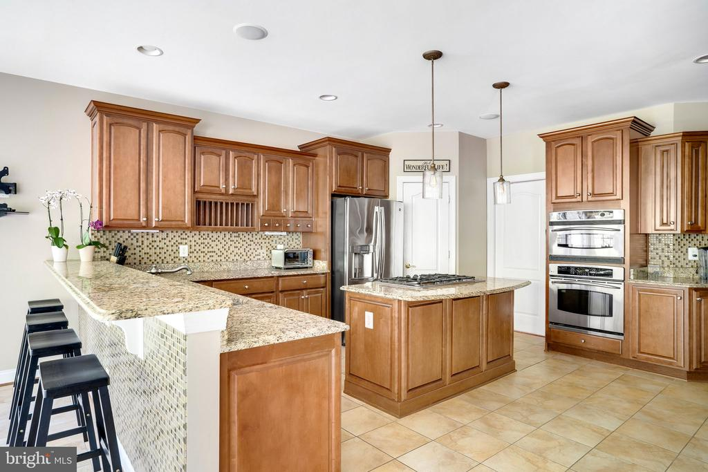 Long counter bar with seating overlooking kitchen - 43768 RIVERPOINT DR, LEESBURG