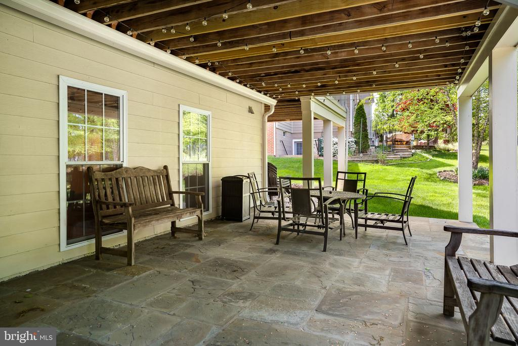 Stone patio under deck has a rain guard system - 43768 RIVERPOINT DR, LEESBURG