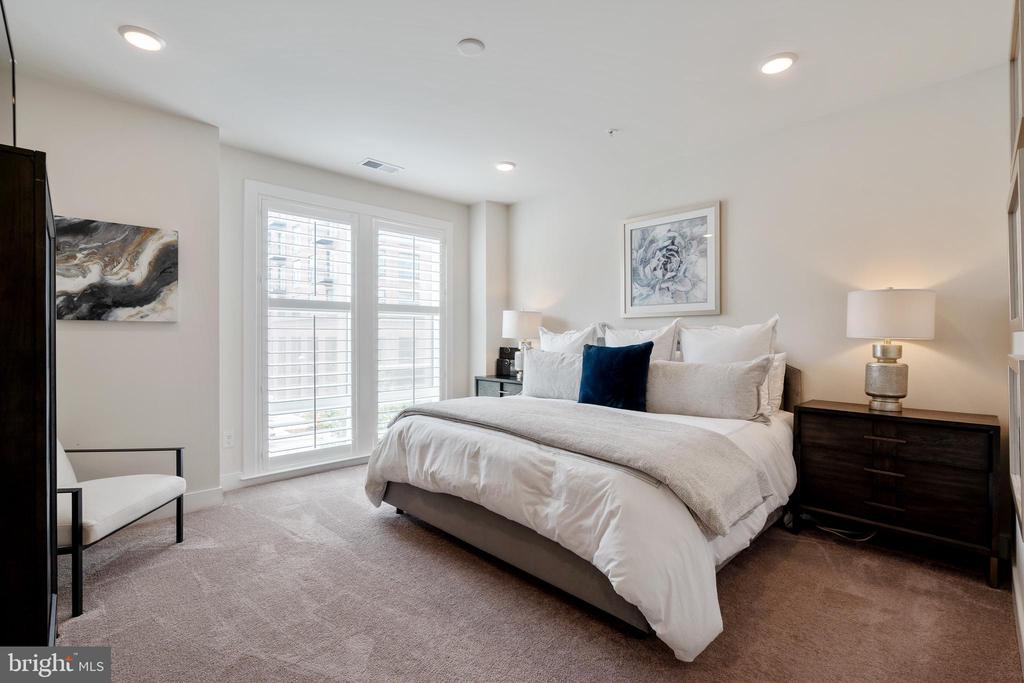 Primary bedroom with custom plantation shutters - 11200 RESTON STATION BLVD #301, RESTON