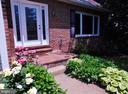 The walkway is lined with beautiful flowers - 102 CHRISTOPHER CT, CHARLES TOWN