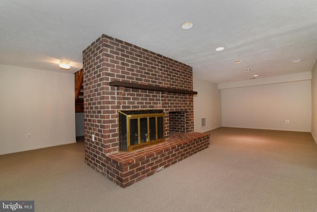 lower level Brick Fireplace - 1101 PEPPERTREE DR, GREAT FALLS