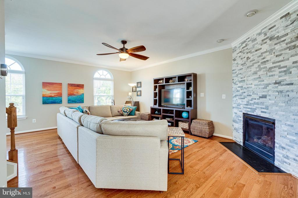 Living room with gas fireplace & stone accent wall - 42965 EDGEWATER ST, CHANTILLY