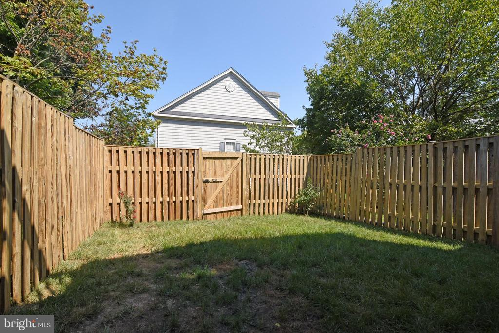 FRESHLY STAINED FENCE WITH DOOR - 112 CONNERY TER SW, LEESBURG