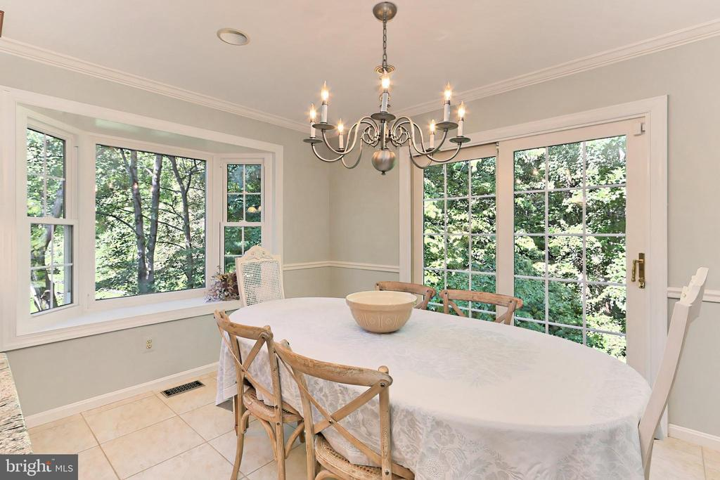 Dining area with chic chandelier & pond view - 9637 LINCOLNWOOD DR, BURKE