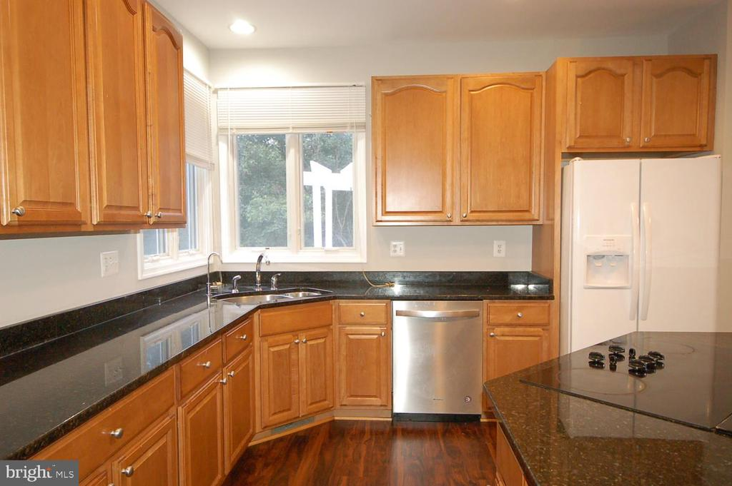 Kitchen with granite counter top and tall cabinets - 8599 EASTERN MORNING RUN, LAUREL