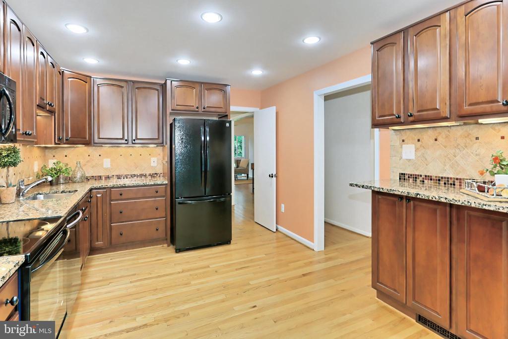 Recessed lights & warm hardwoods frame the kitchen - 11704 NEWBRIDGE CT, RESTON