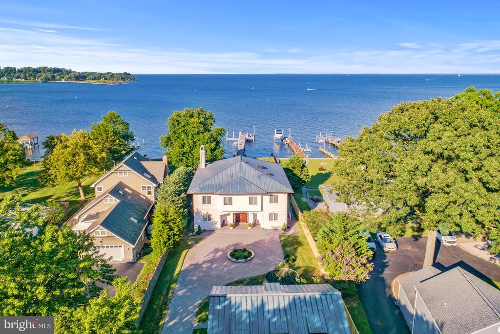 Magothy River Waterfront Built in 2005. This inspiring Mediterranean-style residence offers an enviable location in one of the most desirable waterfront communities in the Annapolis area. Featuring a heated pool granite decking all around, and gracious 150-foot Ipe wood pier. Dakota Mahogany Granite circular driveway fit for accommodating out of town and live-in guests alike, this extraordinary waterfront home is sure to inspire. A home of timeless charm and elegance, the exterior chiseled-face white brick and copper roof tooling evoke a unique blend of strength and sophistication. Inside, sweeping views of the Magothy River and Chesapeake Bay with morning sunrises draw you towards the spacious great room and chefs grade kitchen, appointed with wenge wood and the finest Wolf and SubZero appliances including a commercial grade Hobart Dishwasher and 2 zone wine cooler. With over 5,750 square feet of interior living space, second floor laundry room, and sauna including six bedrooms and six full bathrooms this residence was designed with entertaining in mind. Outside, the picturesque backyard with calming pool and spa, carefully manicured lawn, and solid granite pathways ~ offer an idyllic path to your own private pier, which includes a commercial-grade bulkhead a 40k lb. boat lift and dual jet ski lifts fit for the nautical enthusiast.  For a Virtual Showing please contact listing agent Jennifer Chino 410-941-7009