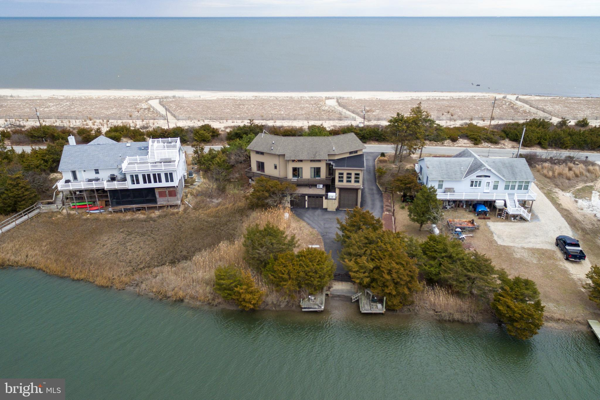 """Enjoy endless sunrises & sunsets from one of Broadkill Beach's most rare waterfront lots that span from the bay to the refuge with water access to the Delaware Bay.   This custom built 3 bedroom home with den/4th bedroom, sunroom and office is a diamond in the rough awaiting your imagination.  Enter to a dramatic 2 story great room with spiral staircase that is flanked by decks which offer incredible views of the Delaware Bay and Prime Hook Wildlife Refuge.  Sunlight streams through the multiple skylights, the perfect start to your day.   The next lucky owners will be delighted to have a boat ramp and dock (DNREC approved) in the back yard, 2 car garage, multi-use high ceiling (boat) garage, extensive heated workshop on lower level (not included in square footage) and a whole house propane generator.  The home has been loved by one family and well maintained over the years (new roof 2003, new HVAC 2017) but is offered in """"as is"""" condition. The septic system has been recently inspected and is in good working order."""
