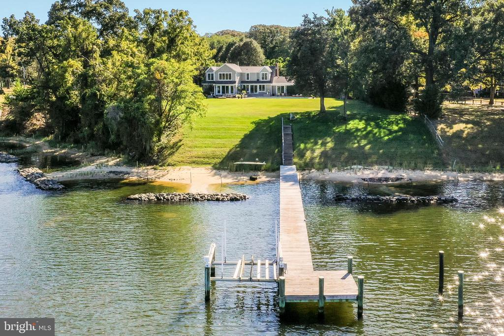 Magnificently sited on level 1.28 Acre lot on Mill Creek with  approximately 200 feet of waterfront, waterside pool, deck, patio, private deep water pier, living shoreline and expansive views of the Magothy River.  Gracious upgraded home with open floor plan,  wood floors and fireplace is perfect for entertaining. Main level has one Bedroom and private office. Spacious master and 2 additional bedrooms on 2nd level, recreation room on lower level. Bonus: Four garage spaces! Steps from Twin Harbors community and beach. Convenient commuting location to Baltimore, Annapolis and Maryland~s Eastern Shore.