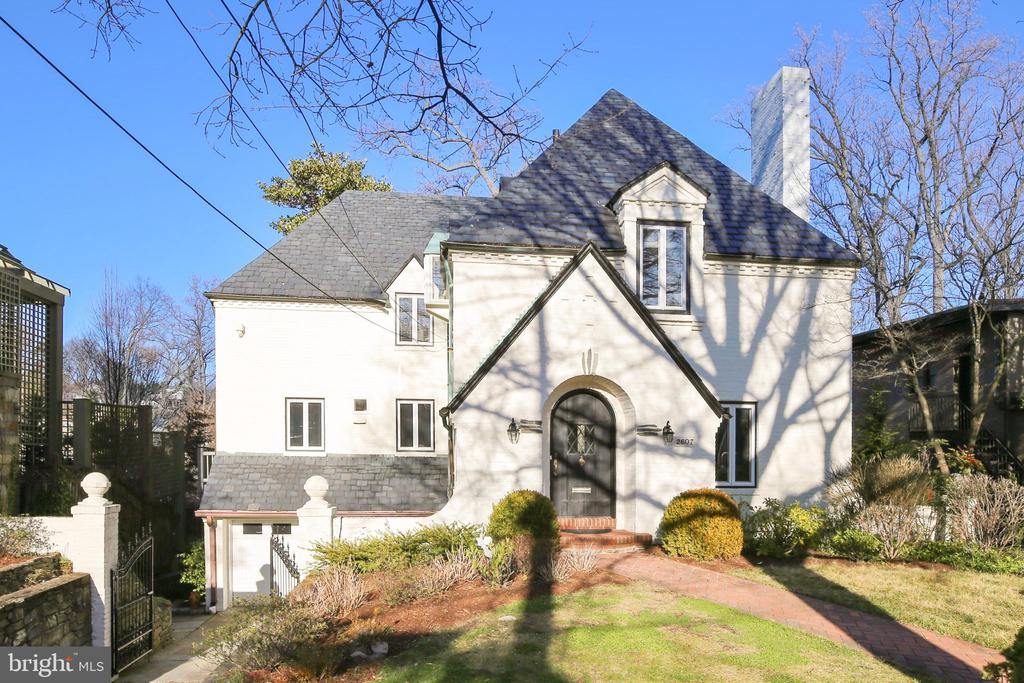 Exquisite French Norman-style Tudor designed by Joseph A. Parks built in 1932 and later expanded.  This 5BR/4.5BA property exudes charm and character and is located on a quiet cul-de-sac lot in sought after Massachusetts Avenue Heights neighborhood with roving security patrol and no HOA. The home features approximately 5,100 square feet of living area on four levels with an attached two-car heated garage and private backyard perched on a hill with treetop views. Special interior features include full in-law/au pair suite with separate entry on its own level, hardwood flooring throughout most of the main and upper levels, custom painting, updated lighting, three fireplaces, custom built-in bookcases, period moldings and striking architectural details throughout. Conveniently located steps to Woodley Park Metro, restaurants, retail, public and private schools, Rock Creek Park, cultural events and neighborhood amenities such as Woodland Normanstone Park.  Covered arched front porch entry leads to inviting foyer with solid oak curved staircase and remodeled powder room; formal living room with gas fireplace and custom built-in bookcases adjacent to separate dining room with bay window; remodeled gourmet kitchen with stainless steel appliances, granite countertops, butler's pantry, and island/breakfast bar area; impressive family room with beamed cathedral ceiling, six skylights, wall-to-wall windows, French door access to rear deck, and staircase leading to lower level recreation room. Upper level spacious master bedroom suite with dual closets and separate dressing room/nursery with private view overlooking backyard; master bath with designer ceramic tile flooring, oversized Jacuzzi tub and shower with ceramic tile surround; second bedroom with paneled walls and built-in bookshelves (perfect for upper-level den as well); third bedroom on this level with cathedral ceilings and staircase to loft/lounge area; updated full bath with tile flooring, walk-in shower with glass