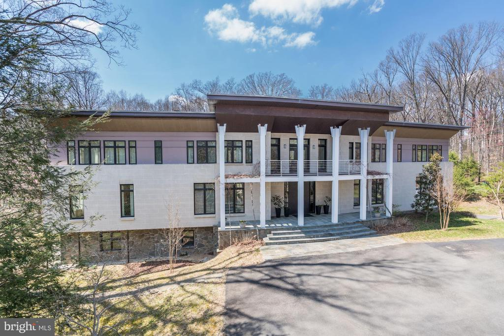 This beautiful, heavily wooded property is offering country-like ambiance located less then 10 minutes drive from Tysons, new vibrant, urban city with signature restaurants and most exclusive shopping malls in the nation.It is easy access to Great Falls national parks, less than 30 minutes drive from Dulles International Airport and minutes from Spring Hill Metro, I-495 and I-66 for short commute to DC and Maryland. Located in a top-rated school district, with well established art community and well attended neighborhood events like free concerts in Great Falls Village, farmers market or artist tours.Exterior design is enhanced by use of top of the art exterior finishes from natural stone, architectural block, copper plated overhangs and 20 foot storefront. It features 10 foot high curved,custom entrance door. Interior finishes with vast Brazilian hardwood floors, marine grade stainless steel railings, granite foyers and marble bathrooms complement contemporary design of the house.Home built in 2007; preserved original structure of 1,000 SF of walk out basement with antique brick floors, 5 foot wood fireplace, and existing 3 bedroom septic field.Over 9,0000 SF and 4 bedroom septic field and new 400+ foot deep well were added.custom designed sculptural stairs, bar and two story great room, as well as flying canvas over stone terrace are very unique and add special charm to the house.
