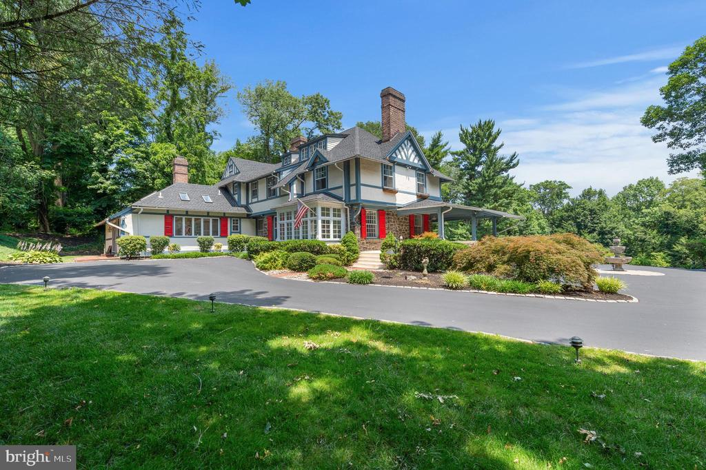 Great New Price for this beautiful Main Line estate commanding a stunning view to the top of a three-acre vista, surrounded by exceptional grounds and garden views. Eldoun is an example of the elegant homes built at the turn of the century by wealthy Philadelphians following the Main Line train tracks from the city. Built for a local doctor, this large Tudor style home has everything for a active lifestyle! Entertain with ease from the large wrap around front porch that leads to the stone patio behind the entire back of the house. This estate boasts room for hundreds and offers expansive living and entertaining space. Old world charm on the interior offers a variety of fabulous entertaining rooms, six fireplaces, hardwood floors, paneled solid wood doors throughout and an expansive kitchen and family room overlooking the property. This home has all newer systems, roof, gutters and electrical. The interior is freshly painted and move in ready! There is plenty of available parking with the long driveway and the circle which is at the top with the three-tier stone fountain. There is additional parking by the carriage house which has its own driveway. Eldoun is conveniently located in walking distance to Radnor train station, Radnor High and Elementary, downtown Wayne and Radnor for local shopping and restaurants and is within proximity to all major roads for commuting to Center City or the airport.