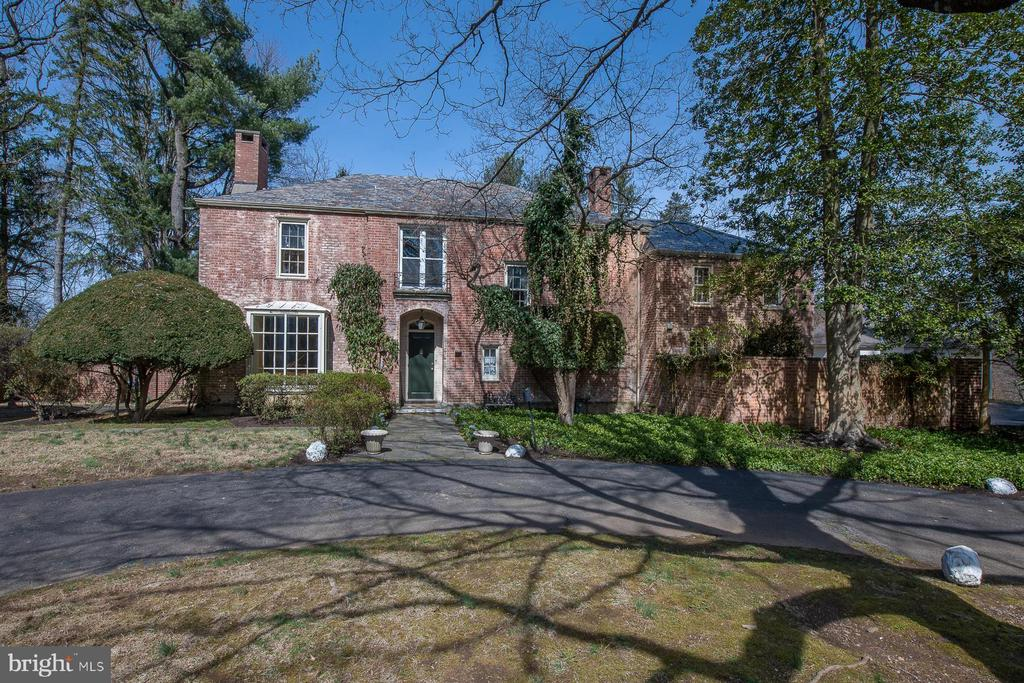 """Classic brick manor home situated on a prime one and a half+ acres on a private cul-de-sac in Villanova.  Originally built by Townsend and Elfreth Company for the Clothier Family of Philadelphia this home is filled with charm and light and wonderful architectural details.  Drive down the impressive circular driveway to the brick covered wood front door. The encapturing front entrance hall features an enchanting curved staircase with palladian window overlooking the front grounds. The entrance hall also leads to the large formal living room with bay window and elegant fireplace with wonderful views of the front, side and rear yards. The entrance hall leads to an inviting study with access to a private patio with awning and the entrance to the large stately dining room which adjoins a country kitchen and breakfast room with outside entrance to the rear driveway and two-car garage.  A Private powder room is tucked under the front stairway. Laundry area and back staircase complete this level. The second floor features a large master suite with private bath and walk-in closet and wonderful views of the beautiful grounds. Second bedroom/office with hardwood floors features a large picture window with views of the front grounds. There are two spacious bedrooms with a Jack and Jill bath in the main section of the house. The original servant's quarters features two bedrooms with a hall bathroom and access to the back stairs. This home is loaded with character and is awaiting updating throughout and personal touches. This home is PRICED TO SELL and is being sold in """"as is"""" condition."""