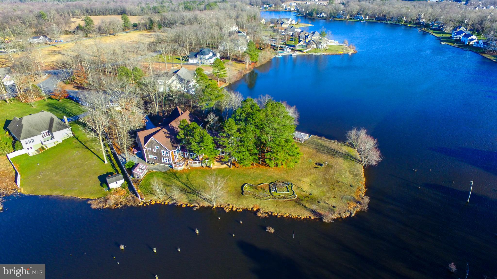 Breathtaking custom built waterfront retreat on a wooded one-and-a-half acre. Step into the gracious foyer that leads to the centerpiece dining room. The great room boasts 24 foot ceilings, wood burning fireplace and expansive natural views. The chefs kitchen is adjoined by a sunroom with gas grill and a walk-in pantry with refrigerator. First floor owners suite with luxury bath and outdoor hot tub on the wraparound deck. Luxurious touches throughout including an endless pool, polished porcelain flooring, mahogany, beech, bloodwood, cherry and rosewood finishes, waterside gazebo and greenhouse. Ascend the curved stairway to the library, a light-filled bedroom, and two suites, one with a kitchen and separate entrance. The home theatre is complete with lounge seating and new HVAC. Dual two car garages. Realize your dream in this captivating home.