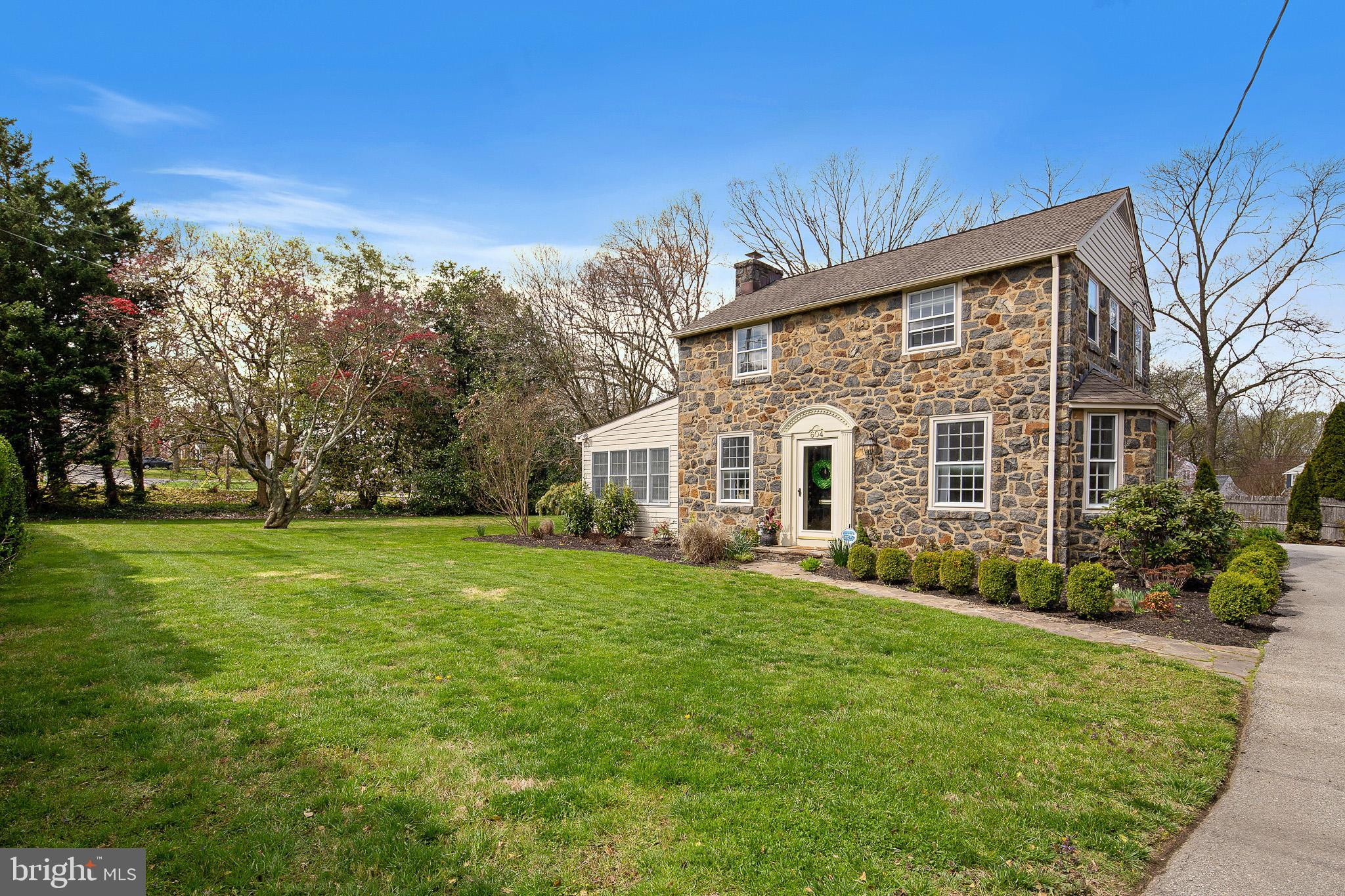 """Please view the 360 virtual tour before scheduling a showing.  https://my.matterport.com/show/?m=cAkTszTh4uc&mls=1.  If you ever wanted character in a home, this is it! This beautiful stone colonial sits on a double lot, which provides a wonderful yard off of the deck, with lots of privacy plantings. The interior is brimming with the warmth of honest materials, like hardwood floors, a stone fireplace, granite, stainless and 42"""" cherry cabinets, great woodwork and good old fashioned real plaster. The sun room is exceptional with its high ceiling, abundant windows, skylights and stone wall, accessing the flowing deck. The beautiful formal dining room lives large with its expansive bay window. Off of the kitchen is the study/breakfast room, also filled with light due to the wall of glass looking out on the yard and deck, and it leads to the over-sized garage.   Alert! This is the home that can handle expansion! The stone garage offers an opportunity for a much larger home for someone with the vision. Recently converted to gas and split system AC. Perfectly located in a one street niche of stone homes that abut the Bringhurst Woods and the Greenway, it is just a hop to highways and access to everything."""