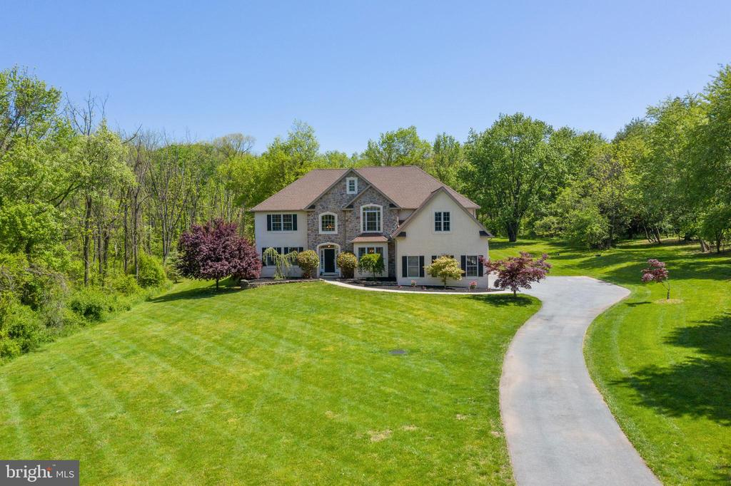 Shows like a Model home both inside and out!! Enter this stunning 10 yr old Center Hall Colonial to be greeted by a stunning  two story foyer w/ grand staircase, gleaming oak hw flooring, arched doorways, extensive millwork inc. coffered ceilings, and chair rail  moldings through most of first floor! Off the foyer you are greeted by the LR(currently being used as an office), and a spacious Dining room.  Most all lighting has been newly upgraded and enjoy @ $11,000 in stunning window treatments. The two story family room, where the coffered ceiling continues, you will find  floor to ceiling windows with views of your private oasis, a stunning floor to ceiling stone gas fp, and built in bookcases. The Gourmet Kitchen and bonus sunroom/eating area boasts custom cabinetry, Granite Counters and tiled backsplash, butler~s pantry w/wine fridge, and  high end GE Monogram SS appliances.  Enjoy entertaining and eating around the spacious center island with 4 stool seating or the bonus sunroom area with access through sliding doors to the exterior stone paver patio. Just in time for the summer to enjoy your built in salt water pool surrounded by close to 3 acres!! A spacious bedroom that can be used as an inlaw/au paire suite or Office can also be found on this level along with a beautifully upgraded full bath. The Second level boasts your Masters retreat complete with deep tray ceiling, recessed lighting, a spacious sitting area and huge walk in closet. The Master BA shows  2 tiered granite sinks, tile surround, soaking tub, and open shower . The third bedroom Princess suite w/ sep bath shows deep closet & the 4th and 5th spacious bedrooms share a full upgraded bath.  Laundry can be found on this level. The full length basement with egress window is ready for your finishing touches. Convenient  proximity to parks,shopping. and major arteries.  An additional .70 acre lot  is included in the sale and not reflected in total lot acres above!