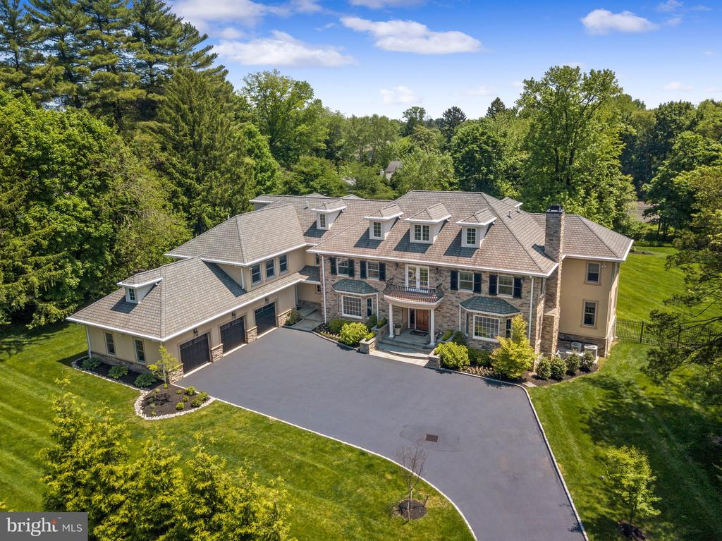 Stately, NEWER STONE MANOR HOME with INCREDIBLE CURB APPEAL prominently set in Haverford~s MERION GOLF ESTATE SECTION in the center of Philadelphia~s historic Main Line. Beautifully sited on 1.2 +/- professionally landscaped and fenced acres, this property takes full advantage of its Southern exposure to offer SUNLIGHT THROUGHOUT THE DAY in a serene, natural setting with complete privacy.  This 10,000+ square foot home is truly unique ~ graciously scaled rooms, 10+ft ceiling heights on three levels, a sun-drenched interior, transverse floor-plan, and an incredible flow make this perfect for comfortable FAMILY LIVING AND GRAND SCALE ENTERTAINING. Luxuriant details are present inside and out, including: handsome stone facade, numerous walls of windows drenching the interior with sun, soaring ceilings, tall doors and arched doorways, extensive crown molding and wainscoting, deep-silled windows, gleaming site finished hardwood floors, designer-sourced fixtures, and imported marbles and granites.Access this 3-STORY MASTERPIECE of 6+ BEDROOMS and 7-1/2 BATHS via lit stone piers and a Belgium block lined drive. Elegant flagstone stairs and a columned portico lead you into a grand 2-story entrance hall with beautiful flared staircase and windowed landing.  Off the entrance hall are a formal living room with marble gas fireplace and built-ins and a large formal dining room with adjoining butler~s pantry ~ the perfect combination for elegant entertaining.  A large, custom painted paneled library with beamed ceiling and built-in bookshelves creates an incredible work-at-home environment for even the most discerning professional. The sun-drenched family room with vaulted ceiling and limestone gas fireplace comfortably opens to the kitchen, enhancing its role as a central gathering place for family and friends.  Living is made easy with a chef's dream kitchen in vintage white maple cabinetry and all Viking professional appliances suited to making any meal; the kitchen is further
