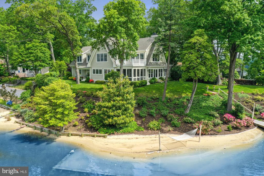 """GLEN-ROBIN ON FOCAL POINT- This exquisite custom designed waterfront residence located on Focal Point is surrounded by 300 feet of waterfront with spectacular, breathtaking views of the Magothy River and Cattail Creek.  If you love boating, fishing, observing wildlife in a natural setting, crabbing on your private deep water pier or just relaxing on your sandy beach in a hammock, this stunning waterfront paradise is just what you have been looking for.  The kitchen was designed by award winning Kitchen Encounters, with oversized granite island including prep sink and microwave drawer, and GE Monogram Stainless Steel appliances.  Watch the sunrise from the master suite roof deck allowing for full enjoyment of the sunsets and cool river breezes.  Additional features include windows galore-to maximize water views; hardwood floors; waterfront screened porch for """"al fresco """" dining; family room with wood burning fireplace and built-ins; 4/5 bedrooms; four full baths; 9 foot ceilings; 2X6 framing; an open, flowing floor plan; and a home office/study on main level (which could serve as a fifth bedroom).  A covered porch, leading from the dining room, is perfect for enjoying cocktails before dining.  There is expansive space above the garage on the second level that could be finished to the new buyer's specifications, if needed.  The private and serene setting with professionally designed landscaping, complete this pristine luxurious retreat.  Conveniently located to BWI Airport, Baltimore, Annapolis, and DC.  Severna Park """"Blue Ribbon""""schools."""