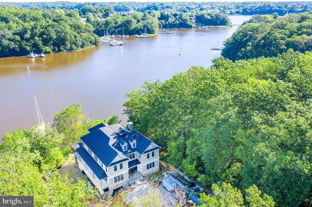 """Absolute privacy in the heart of Annapolis.  Over 6 acres with 350 ft of water frontage on Clement's creek.  Spectacular panoramic water views with western sunset exposure.  Deep water protected pier with 8 ft water depth, IPE decking, 60' x 15' slip, 2 boat lifts, 2 jet ski lifts and shore-power with 60 amp service.   Clement's creek provides easy access to the Severn River and Downtown Annapolis.  Over 350 ft of stone rip rap recently installed.   New custom 10,000 sqft. home has been built with 10 ft ceilings on all 3 levels plus a 4th level loft area.  Elevator service to all 4 levels.  The exterior is almost completed; Hardie shingle siding, stone facade, top-of-the-line windows & roof is in place.  Exterior perimeter concrete walls & Geo-thermal wells have been installed.  The interior has been framed and HVAC duct work installed.  Seller is selling the home """"AS IS"""" and the work on-site has been paused.   The rendering images reflect the architectural plans that the seller had prepared.   Architectural drawings, site plans & all materials on-site convey with sale.  This is an amazing opportunity to take over the direction of this new custom waterfront home and select finishes to meet your style and taste.  Don't let this one slip away!"""