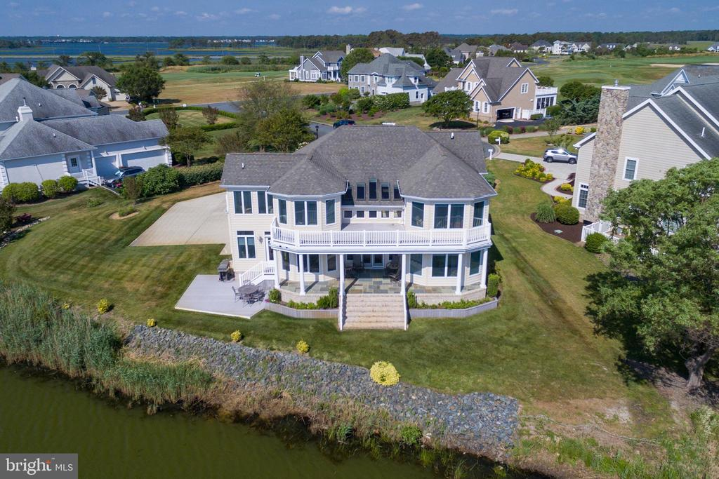 Luxurious waterfront home in the prestigious golfing community at Lighthouse Sound! This 5 bedroom 3 1/2 bath home over looks the pond and the bay with  spectacular panoramic views of the Ocean City skyline! From the time you take that 1st step inside you will be taken back by the attention to detail in every direction. The open floor plan on the 1st floor features custom hardwood floors, a study/den, a well appointed 1/2 bath, a master suite, a beautiful living- dinning-kitchen area and cozy sun room with great water views. The living area features a gas fireplace with stone surround and vaulted ceiling with a French Door that leads directly out to the covered porch with elegant pillars where you can walk directly out to the back yard. The gourmet  kitchen is the center piece of the living area. The Wolfe gas stove with  griddle, microwave and convection oven with pizza stone and heat lamp make this kitchen a chef's dream! Also featured is a Kitchen Aid subzero refrigerator, dishwasher and wine cooler. There is a beautiful back splash and under counter lighting. The custom dark cabinets with pull outs and gorgeous dark granite make this area a showplace! The master suite features windows in every direction and a large custom bath with ceramic tile, double vanity, tiled shower and a whirl pool tub. The custom ceilings through this luxury home are fantastic. Upstairs you will find 4 bedrooms, 2 full baths , two outside decks and again windows everywhere with  beautiful water views. The laundry room is on the 1st level as is the entrance to the over sized 2 car attached garage. When you step outside you truly appreciate the awesome views and tranquility of the beautiful setting overlooking the water, golf course and the bay. You really must see this very special property for yourself to appreciate everything it has to offer!