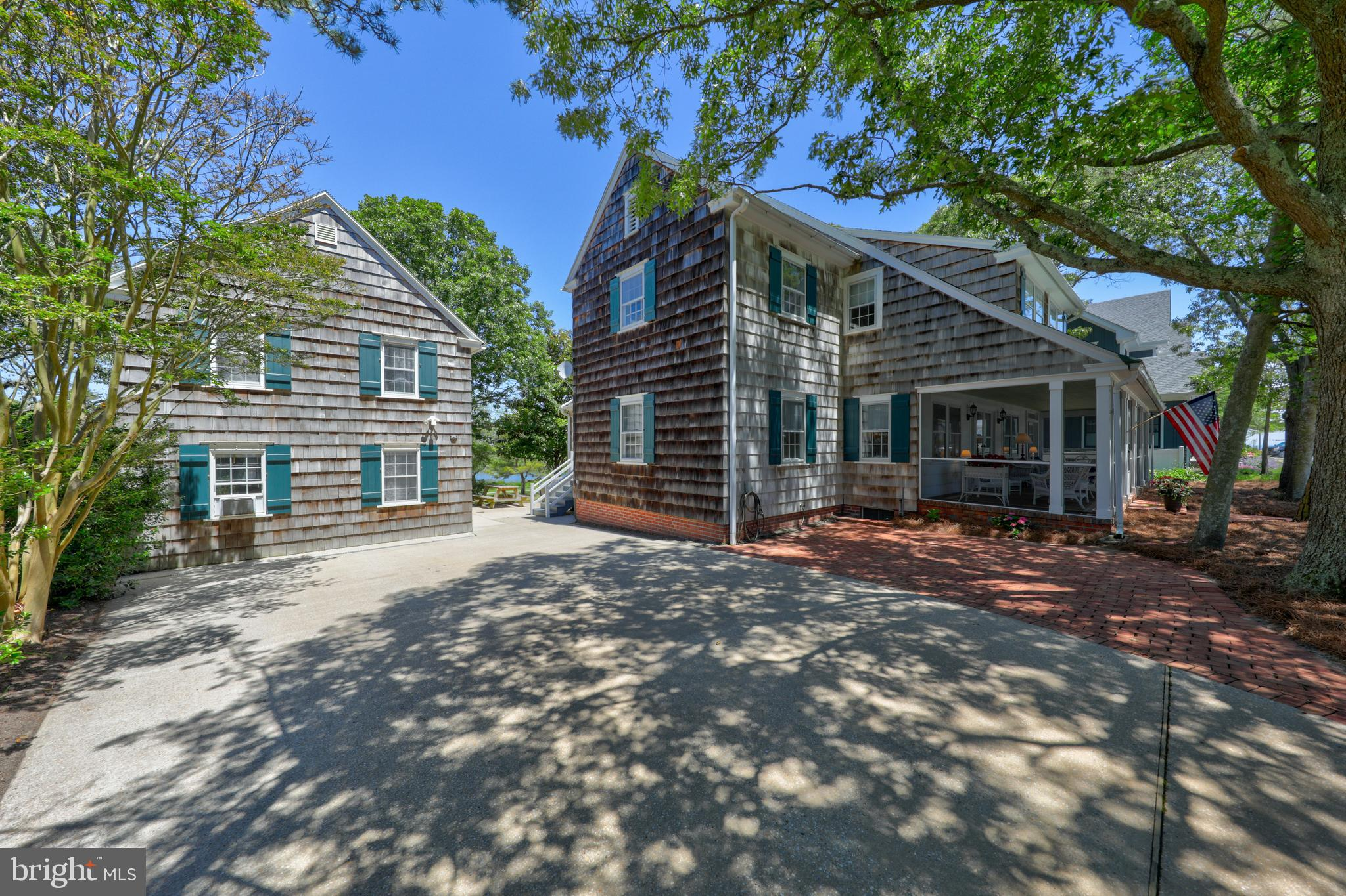 The living is easy in this impressive 8 bedroom ocean block coastal compound perfectly positioned to enjoy lovely Lake Gerar views and located within a level stroll to the sand and surf.  The gracious 6BR main house is situated on an oversize 75x100 lot featuring a quintessential, wraparound front porch, sizeable living room with wood burning fireplace, generous dining room, large kitchen facing the lake,  butler's pantry, den, 1/2 bath and a first floor master suite with full bathroom. Upstairs you will find 5 additional bedrooms, three baths and a sitting area plus a second floor terrace with lake views.   The cozy, detached cottage is perfect for overflow guests and features 2 bedrooms, full hall bathroom and outdoor shower.  Perfect for a family or as a holiday retreat, this property is ideally positioned to enjoy the proximity to the beach, cafes and restaurants and premier shopping.