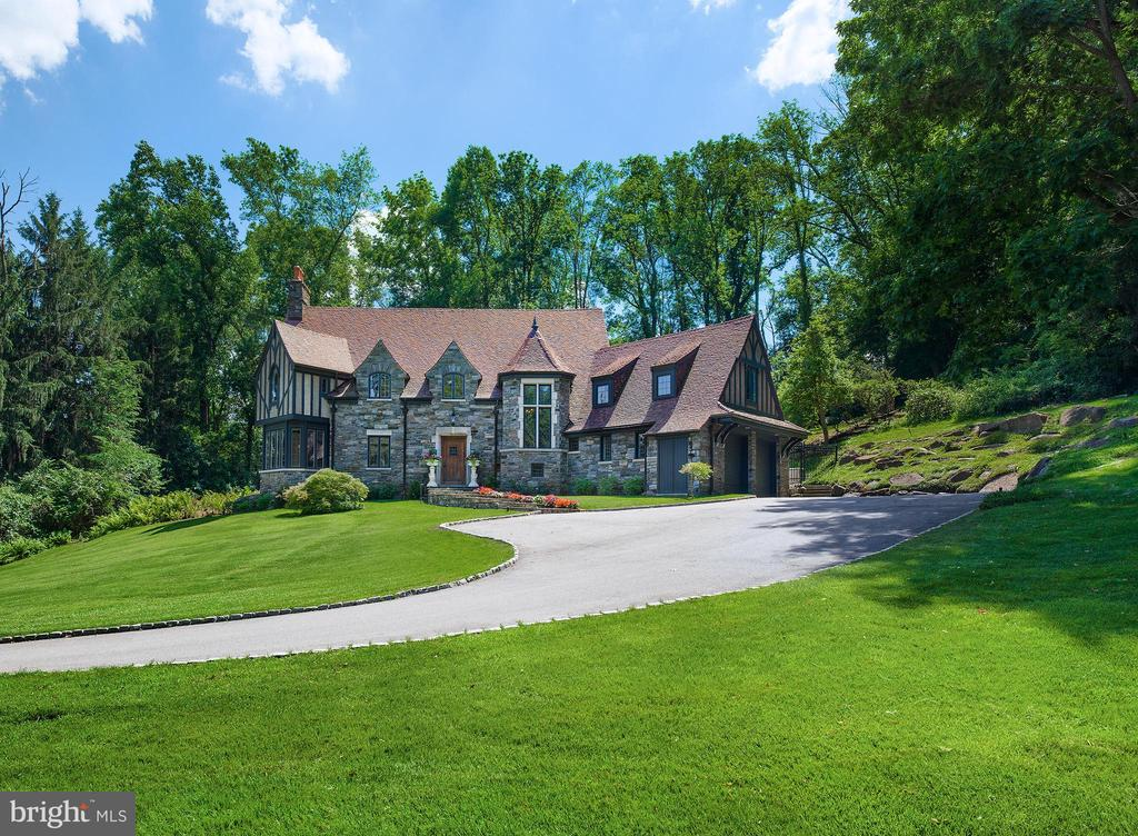 This stunning and stately stone Tudor-style Colonial, designer by Fred Bissinger and hand-crafted by E.B Mahoney, is set  on pristine manicured grounds in Villanova and features gorgeous architectural elements and incredible character. A sweeping driveway welcomes you home and winds to an oversized 2-car garage with peaked roof. The spectacular 1.56-acre property graced by mature trees, lush greenery, beautiful gardens and hardscaping is a breathtaking backdrop for this truly distinctive residence. A lovely flagstone walkway lined with flowers and tasteful lighting brings you closer to the fa~ade~s exquisite stonework and escorts you to the commanding wood front door. Graciousness and elegance envelop you the moment you step into the entry hall with wood beamed ceiling and stone floors. Beyond awaits a magnificent great room accentuated by airy ceilings, striking exposed wood beams, and open living and dining areas with the stone flooring continuing throughout, affording a perfect flow for entertaining. Relax with company in the light-bathed living room around the fireplace, and sip a cocktail in the charming sitting nook nearby surrounded by windows and showcasing the views. Move seamlessly into the dining room for formal sit-down meals, brightened by a wall of glass with doors leading out to the fabulous paver stone patio and sprawling rear lawn. The cook~s kitchen is stylish and functional, with extensive wood cabinetry and pantry space, a huge center island with seating and storage, farmhouse sink, and premium appliances including a stainless Viking 6-burner range, 2nd convection microwave/oven and built-in fridge. Completing this level is a large refined powder room, big laundry room with a 3rd oven, sink and cabinetry, and sun-filled greenhouse room for your favorite plants. Ascending the main staircase of rich wood, a tall window of leaded glass brings light in. The carpeted 2nd story presents 4 bedrooms and 3 full baths for the comfort of family and overnigh