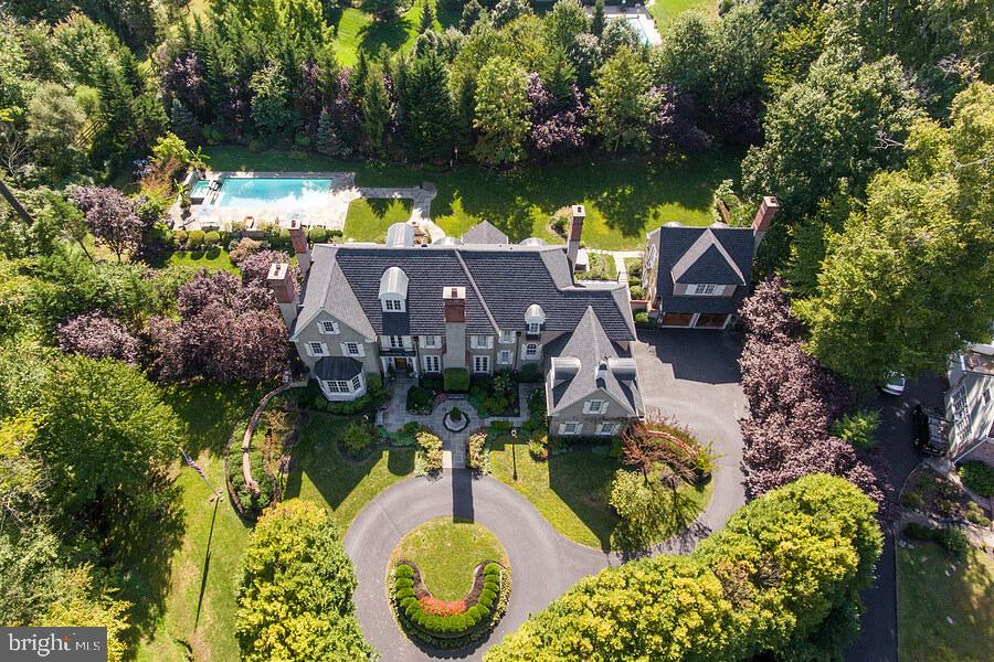 Welcome to 785 Harrison Road - Now More than Ever, there is no place like Home & this Legacy Worthy Property is Truly A Family Compound and Vacation Home for the Ages!  It exemplifies impeccable design; every possible modern amenity with classic architectural detail and elements executed to perfection on a breathtaking private lot in one of Radnor Townships most coveted neighborhoods. The property was designed and built by two of our regions finest; Michael Visich Architect and Pohlig Builders. This collaboration combined with period sourced architectural treasures, and premier landscape design talent results in an irresistible Estate Property!  An impressive allee of trees lines the circular drive entry to the property that includes; the five Bedroom Main House and  one bedroom Guest House, 1+ acres of glorious, manicured grounds with resort quality outdoor living including a heated pool with waterfall feature, expansive flagstone terraces, two outdoor fireplaces and total privacy.  The Main House is a classic two story colonial with open floor plan, 10 foot ceilings on the first floor, beautiful millwork throughout and 5 fireplaces. The front to back grand center entrance hall opens to the formal living and dining rooms, and library - all with fireplaces and hardwood floors.  The  gourmet kitchen is beyond compare and features glazed brick walls, Kountry Kraft 42 inch custom cabinetry, a pair of 36  inch subzero refrigerators, Wolf Gas Fired 8 Burner Cooktop with copper hood, stainless steel island with freezer drawers, multiple appliances, two dishwashers, a large pantry closet, a light filled breakfast room that opens to the step down family room with fireplace, and built-ins.  The family entry/mud room includes an entrance to the 3-car attached garage, family half bath, closets, built-ins, laundry closet, and secondary staircase to the second floor and basement. The second floor includes a private master suite with fireplace, sitting area, built-in's, 2 walk-in