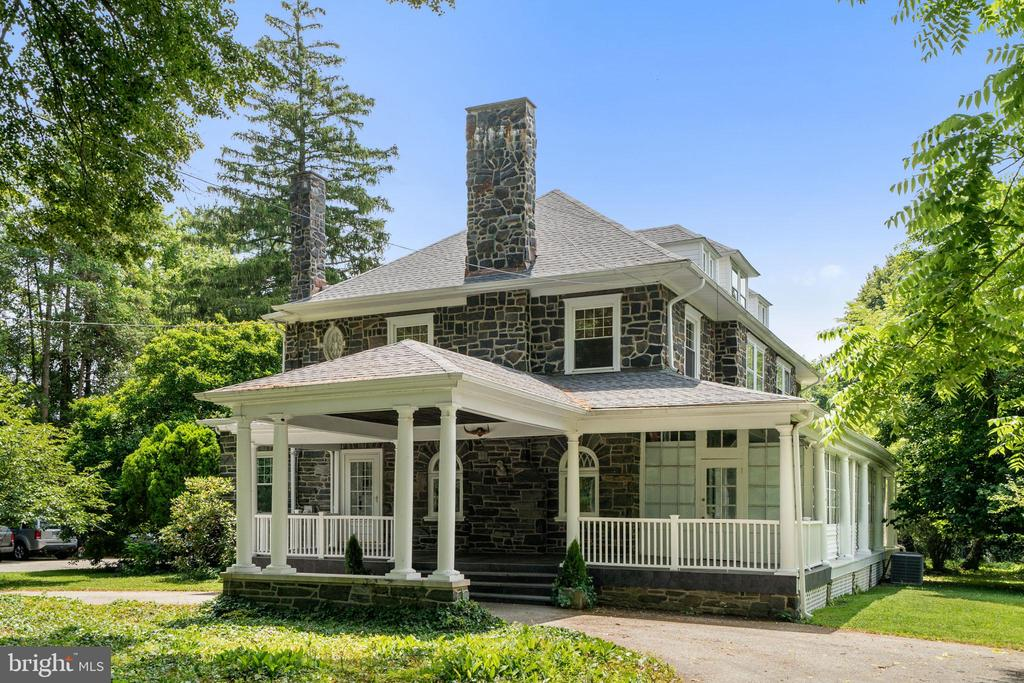 **Showings Begin 7/16 - Grande Stone Colonial with romantic large covered porches, columns, ornate moldings, 10 ft+ ceilings and many large decorative windows set on approx 1 level acre of lush private property in Haverford's Merion Golf Manor neighborhood. Pictures simply do not do justice to this beautiful estate with its landscape brimming with trees, bushes & expansive green lawn. This turn-of-the-century home boasts 20-inch thick exterior stone walls, multiple sunrooms, and 6 beautiful fireplaces. This estate has been lovingly maintained & is impeccably preserved and updated to maintain the charm, integrity & authenticity of its era. The front of the home has a dramatic drive through portico and circular drive complemented by generous driveway parking for guests. Exquisite architectural details abound inside, enhancing the unique character with a colonial oak wood staircase, stunning trim & woodwork throughout, deep window sills, walls of glass french doors, beautiful hardwood floors, & pocket doors among the distinctive elements. The grand foyer features a solid wood and glass front door, fireplace, window seat, built in bookcases and a powder room. Enter the spacious living room with coffered ceiling and wood burning fireplace opening to a sunroom that runs the length (depth) of the house. Pocket doors open to an elegant dining room with a wood burning fireplace and wall of glass french doors opening onto a large patio making entertaining indoors and outdoors seamless. The dining room opens to a sitting room with a built-in window seat and picture window. The sunny eat-in kitchen has ample cabinetry & prep space, plus a new gas range with oven and breakfast room. Beyond affords access to a laundry room, driveway access to the sunroom/mudroom, and the back staircase from the in law suite that opens into the kitchen as well. From the living room access the original staircase ascending to the 2nd floor landing. The versatile second floor houses 5 bright, comfort