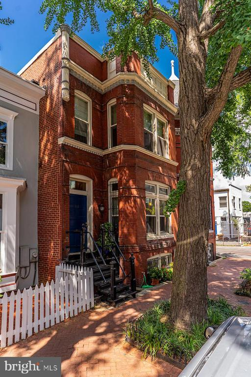 OFFERS DUE  by 4pm Thursday, July 23, 2020.Absolutely charming 20 ft. wide row house renovated in 2002.   Features include newly refinished pine flooring throughout, gas fireplace with vintage mantle, elaborate crown molding, tall ceilings, pocket door, exposed brick walls in kitchen and stair wall.   Great lighting fixtures throughout.  First floor: Entry with coat hooks, charming hall with exposed brick wall up stairway, hall closet and half bath.  A cooks kitchen with Stainless Viking stove, Bosch dishwasher and GE Twin Chill refrigerator and central island in kitchen. and adjacent laundry room with pantry storage.   Living room and dining area is spacious with gas fireplace. and vintage mantle.  Upstairs is a large master bedroom with walk-in cedar closet and built-ins.  A home office is entered thru glass French doors and has work stations for two.  The 2nd bedroom is bright with armoire closet.  Full bath features lovely white and grey tile and white wainscoting.  The basement offers and entry hall with access to an owners storage/work room and entrance to the 1 bedroom unit that is separately metered, has a gas stove fireplace insert  for cozy winter nights and central HVAC .   This unit has a Certificate of Occupancy.    If the new owner wishes to have all 3 floors turned into a single family home, a staircase can be reinstalled from the main floor hall closet and into the workroom below-ask agent how this was laid out by owners.  In the back is an owners deck and garden; BBQ, table, chairs, and lighting convey as well as flat screen TV in living room,  armoire and hall cabinet on top floor.  There is access to the alley for trash/recycling.