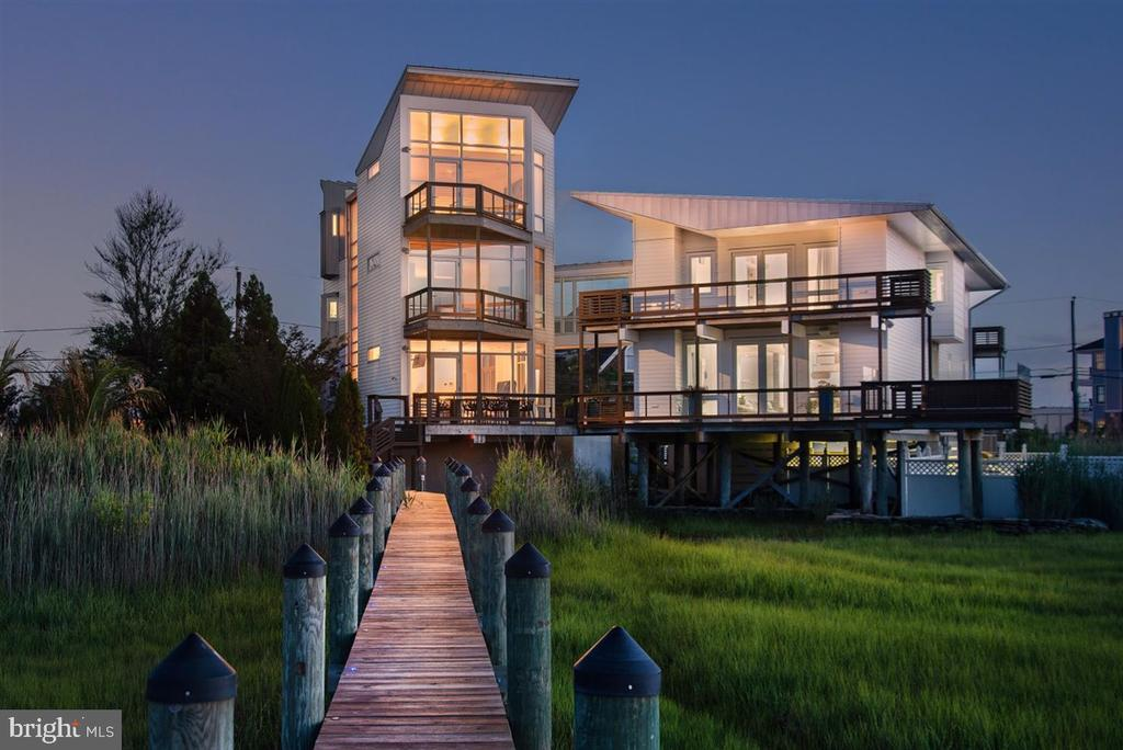 Ideally located on the bay in the White Marlin Capital of the World, also known as Ocean City, is where you'll find this meticulously designed home. This soft modern five-bedroom home with over 6000 square feet of living space offers a private getaway while being close to fine dining and shopping. Over $150,000 in upgrades in 2020 featuring all new Elan Smart Home Technology System and Lutron Integrated lighting. Constructed with masterful craftsmanship using the finest materials curated from across the world, the interior living space seamlessly connects to the outdoors. Iconic designs by Boffi are demonstrated in the designer kitchen and master spa bath. The third floor Master Suite is a serene private retreat, with its private deck encasing bay views. All five bathrooms showcase world class fine material and timeless design. The black bottom saltwater pool provides resort-level living in the comfort of home and the private pier captures picture perfect views of sunsets. High performing standing seam metal roofing, concrete floors and steel beams reassure for a safe and sound home. Call the captain and have him meet you across the street at the Marina, which can be seen from the southern side of the home, and enjoy the day exploring the waters surrounding Assateague Island or find that White Marlin. A truly captivating property to inspire an incomparable life of discreet luxury.