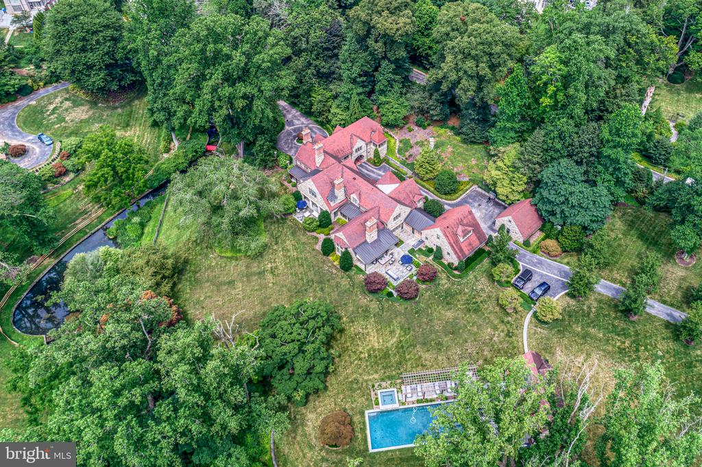 Magnificence awaits you at 135 Cheswold Valley Road, an exquisite sprawling stone estate home beyond compare. Gracefully perched on 4 gorgeous park-like acres with a sparkling resort pool, relaxing spa, pergola and pool house, rests this rare and breathtaking gem, affording an unrivaled luxury oasis in a highly coveted Haverford locale. Tucked away behind the gates of a long and winding tree-lined drive, this remarkable residence is marked by a circular motor court, lush landscaping, and elegant archways beckoning you inside. Awe-inspiring architecture and incredible outdoor living spaces define the upscale retreat, which is masterfully built with every luxury and convenience in mind. Grandeur and refinement are reflected inside and out, down to the last detail of this one-of-a-kind stunner boasting 5 to 6 bedrooms, 7.4 baths, and gracious living and entertaining rooms. Sun-bathed interiors are truly a work of art, enriched by impeccable millwork, beautiful wood flooring, the highest-grade fit and finishes, and generous windows throughout inviting in lovely natural light. The formal entry with a distinctive custom ceiling provides a warm welcome. Host guests and spend family time in the fabulous great room nearby featuring ceiling beams, an open-concept dining area, walls of French doors overlooking the manicured grounds, and sitting area with a stately fireplace setting an elegant tone. For the chef, a sophisticated gourmet kitchen is a knockout, richly appointed with top-of-the-line, built-in stainless steel appliances, white custom cabinetry, thick slab counters, expansive center island with storage and breakfast bar, plus a dramatic coffered ceiling. All of this is anchored by an imported La Cornue, a culinary showpiece! Cook and serve with ease, whether throwing a dinner party in the formal dining room or sipping coffee in the breakfast nook with built-in banquet large enough to seat a crowd. Equally impressive is the striking family room just off the kitchen, 