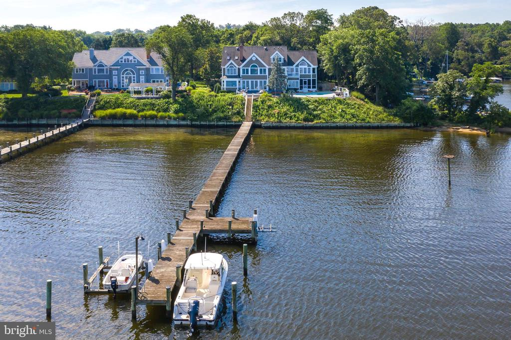 RARE OPPORTUNITY TO OWN A SPECTACULAR RIVER FRONT ESTATE IN A HIGHLY SOUGT AFTER LOCATION. Breathtaking panoramic views with western sunset exposure. Elegant and private setting and graciously sited on .62 acres. You will love the waterside, saltwater heated pool and spa with ample decking and unobstructed views of the Magothy River/Forked Creek and Cool Springs. 128 Feet of water frontage, bulkhead and deep-water private dock with two lifts. Enter this beautiful home through your custom, cherry wood double doors to view straight down the Magothy River.  Over 6000+ square feet on 4 levels with waterside office, large crown molding and screened porch for al-fresco dining and lounging.   This 5BR, 6FB home has an elegant coastal / transitional style with open floor plan and private bath for each bedroom. The Owner's suite has a lovely elevated water view, cozy gas fireplace, remote controlled black out blinds and walk-in closet with washer / dryer.  Gorgeous waterside 3rd floor TV/family room above the garage is a wonderful second family space with gas fireplace and rolling library ladder to access the fourth floor balcony. Fabulous renovated basement with new kitchen, bedroom and full bath that is perfect for guests, nanny or in-law suite. Beautifully landscaped with a tree-lined drive showcasing cherry trees, evergreens, boxwoods and perennial tulips. Teaming with year round visual interest from a variety of boats passing by, Chesapeake Bay wildlife and Wednesday night sailboat races.  All can  be seen from just about every room in your home! Located in a highly sought after community of fine homes and close to all major commuting routes, restaurants and shopping. Ulmstead offers a multitude of social events, 2 marinas, a pool, clubhouse, horse facilities; tennis/pickleball courts ball fields and a waterfront beach park! Just 5 miles to downtown Annapolis and Severna Park, and convenient to Baltimore, BWI, Ft. Meade/NSA and Washington, DC.
