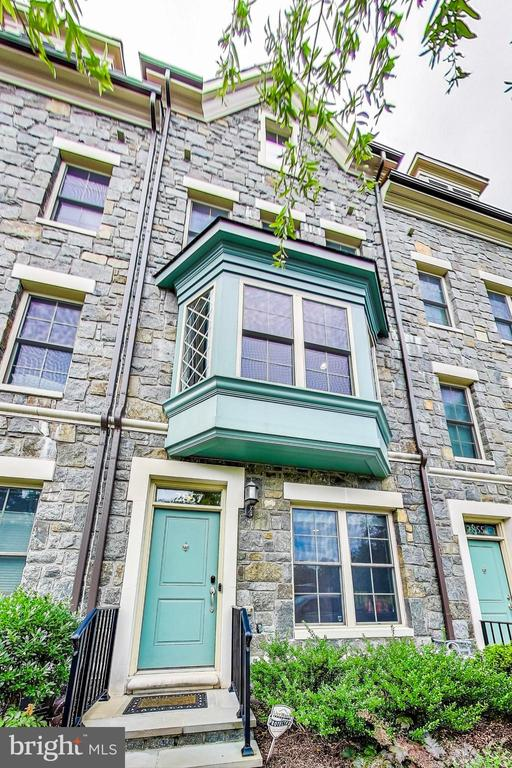 3D tour can be seen at  https://real.vision/2857-chancellors-way-northeast?o=u  Absolutely the best view in Chancellors Row! One of the stone houses with a gabled roof!  A  truly rarely available home with stone facade matching the historic facade of St. Paul's College. Stone steps lead up to the front door with glass transom above. Inside, a beautiful LEED-certified home built by EYA.  Immaculate and in move-in condition. Gleaming hardwood floors grace the entry level with double doors leading to the spacious office/fourth bedroom. The gorgeous hardwood staircase leads to the open main level with bright north/south exposure. Here the cook-friendly  kitchen has plentiful white cabinetry, granite counters, subway tile, breakfast bar, pantry, recessed lighting, and a glass French door to the deck with a gas line for grill. The dining  area is open to the living area  which is highlighted by the front bay window,  one of only three in Chancellors Row! The main level also features a  gas fireplace with custom built-ins,  recessed lighting, and hardwood flooring.  Upstairs, the owner's  suite includes a  walk-in closet, hardwood flooring, overhead lighting and bath featuring a walk-in shower with built-in bench and rainfall shower head, and a double bowl vanity.  The second bedroom suite features hardwood flooring, overhead lighting, closet and full bath. The laundry closet with stacked washer and dryer is conveniently located on this level. The upper level loft/family room/third bedroom features hardwood flooring, recessed lighting, wide sliding glass door to the spacious tiled rooftop deck, and a full bath. Over 35K in  upgrades since 2016 including hardwood floors on first floor and in 2nd bedroom; refinished all floors; gas fireplace with custom mantel and cabinetry; new shower door in master bath; all outlets with tamper resistant receptacles and all switches with Decora rocker switches;  composite deck tile on 4th floor roof deck;  2 nest thermostats;  nest doorbell w/camera and keypad; all new light fixtures;  custom  Savannah shades in bay window and 2 third floor bedrooms. The attached one car garage even has an electric charging station.  Three visitor parking passes convey.  An extraordinary opportunity to own in an unbelievably tranquil setting . And an extremely  convenient location within walking distance to the Brookland Metro and just over three miles to the U.S. Capitol.