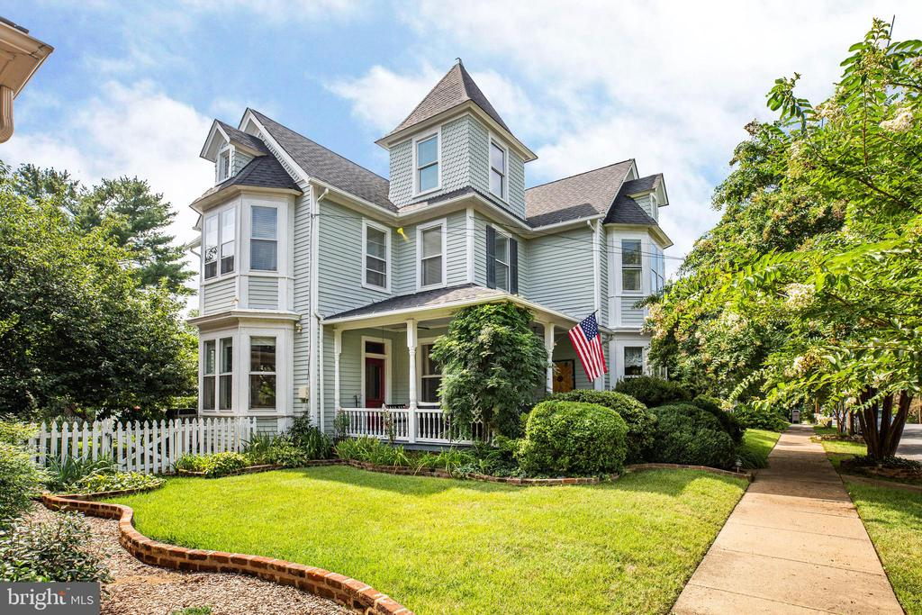 This Historic Queen Ann home was built in 1899 and the entire interior has been completely updated by the current owner,  a well regarded Interior Designer in Fredericksburg. The home is colorful and bright and is simply CHARMING! The house sits in the middle of a double lot, rare for downtown, offering spacious side yards on both sides of the house along with a large private backyard. The front porch, with it's ornate trim work,  is a true delight with porch swing and sectional couch, great for morning coffee, afternoon tea and visiting outdoors.  The large fenced backyard offers a big wood deck, nice stamped concrete patio with fire pit, a covered gazebo area great for grilling and seating, play set, and even more yard for relaxing, playing and entertaining. The adorable 2 car detached garage / carriage house has upstairs storage and it's own electrical system, matches the house in design and has a stamped concrete driveway, offering plenty of off street parking, hard to find downtown! Beautiful landscaping with mature trees and bushes surround the house. Cherry Blossoms, crepe myrtles, rose bushes, hydrangeas, figs and more!  A beautiful and peaceful setting, with an 11 zone sprinkler system  covering all garden beds and lawn to keep it well maintained. The inside of the home is just as charming.  High ceilings with large original crown molding, beautiful woodwork, pocket doors, original banister and staircase, wavy old glass windows, a back staircase, three working gas fireplaces, tons of storage,  Dacur 6 burner stove, comfy sun room, original hardwood flooring recently resurfaced, arches and doorways, cubbies and so much more! An addition to the home is the finished attic / third floor and has three additional ADORABLE bedrooms and sitting area/play area with t.v., one of which is a turret room. This third level is a child's dream space! The Ultimate place for sleepovers, grandchildren parties and kids of all ages, teenagers will love it too! All the windows have character and lots of lighting, The ceiling is insulated with Isonine for added insulation and soundproofing and the space is heated by three mini splits. A basement renovation adds yet another entertainment area, a movie room with over sized couches and t.v. with brand new carpet. A large storage room and a work / hobby room.  The entire home is bright with natural lighting and large windows.  The main level has potential for a Master suite and full bath with private entrance. This space used to be a dentist office back in the day. Today those spaces are the family room and study. The study is plumbed for a full bath. The grand Dining room and living room are joined by original pocket doors. Great spaces for entertaining. The kitchen with it's tall cabinets has been updated with all new Stainless steel appliances and a 6 burner Dacor stove and two side by side ovens. The upstairs houses the four main bedrooms and a beautiful open landing that is yet another comfy space with a huge couch and t.v.  Working remotely these days is made easy in this home, as there are so many private spaces and places to go. Location, location, location! Literally steps away (2-3 blocks) from shops and restaurants downtown! 1/2 a mile from the train station,  one block between Historic Kenmore and The Mary Washington house, This is Downtown living that has it all.