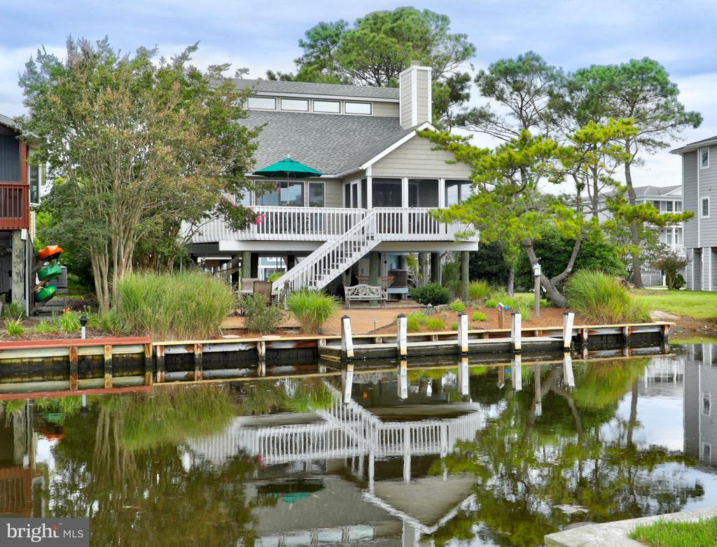 Delightful canal front home with a private boat dock located just a few blocks to the life-guarded beach in South Bethany. This coastal home features an inviting open floorplan with vaulted ceilings, gorgeous hardwood flooring throughout, cozy wood burning fireplace, and new stainless steel appliances (new oven to be installed soon). With a freshly painted interior and exterior, this home is ready to be enjoyed! Incredible outdoor living spaces include a screened porch and deck overlooking the canal and a large waterfront patio deck creating the perfect space for entertaining or relaxing with fantastic water views. There is also an oasis under the home to lounge in hammocks, play games, or host crab feasts. Walk to the beach or spend the day on the bay with the convenience of docking your boat at your back door. This is the perfect beach retreat, tucked away on a quiet street and just a short bike ride to shops and restaurants.