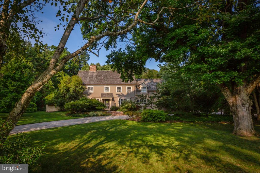 Understated elegance and luxurious amenities await you in this Haverford Colonial, located on one of the Main Line's quintessential streets. A beautifully landscaped yard and secluded pool area are among several outdoor gathering spaces on this well-maintained property. Featured in the opening scene of the award-winning movie Philadelphia, this home is within walking distance of much of the best that the Main Line has to offer.  The sun-filled foyer extends a warm welcome. Stunning wood floors begin in this entryway and continue throughout the home.   A cozy study features plenty of built-ins, a brick fireplace with a white wood mantel, and a large, deep-silled window with views of the expansive front yard.   Plentiful windows in the traditional living room invite nature indoors, making the space feel like a sunroom. The dining room offers plenty of space for holiday meals, as well as French doors leading to a patio with lovely views of the garden.  An informal living area - ideal for everyday gatherings and entertaining - provides an open-concept flow between the kitchen, breakfast room, and fireside family room. Large windows and French doors to the pool area let in lots of natural light. The thoughtfully renovated kitchen includes a vast island with bar seating for five; an apron sink under a triple window that overlooks the lovely front yard; Wolf and Sub-Zero appliances; a double oven; and even a pot-filler over the six-burner gas range. High-quality inset cabinetry offers plentiful storage. Next to a charming window seat, a built-in desk provides a home-office work space.  A large mudroom with built-in storage and a powder room with a sink set within an antique, half-round table complete the main floor.  Upstairs is the master suite, enhanced by a window seat and a massive walk-in closet. The luxurious master bathroom includes an oversized shower, soaking tub, and double vanity. There are three additional bedrooms on this level - each with an en suite bathroom
