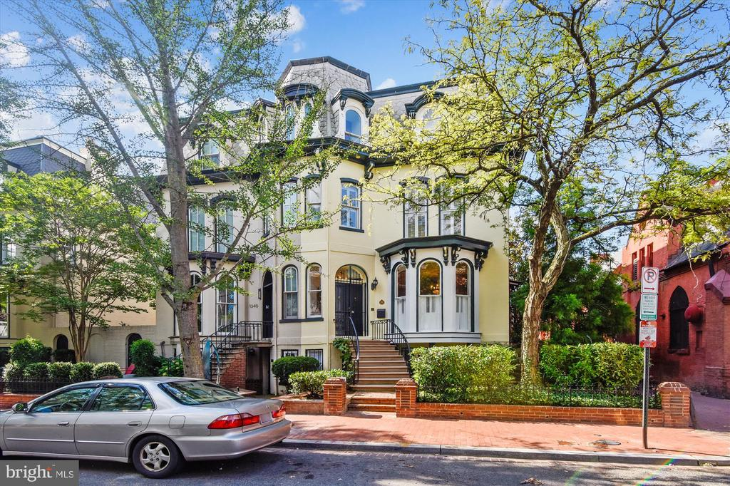 Rare opportunity to own a pristine semi-detached Queen Anne Victorian rowhouse with a 2-story rear carriage house and a lower-level apartment in the main house (both providing rental income) for a total of 7 bedrooms and 5.5 baths, PLUS 2 parking spaces and an abundance of private outdoor living space -- all on a charming tree-lined street in prime Logan Circle/14th St location just 1 block to Le Diplomate and 3 blocks to Whole Foods. **** Main house comprises 3 levels of generous above-grade living space with 4 bedrooms, 3.5 baths, 3 fireplaces, 2-zone heat/AC, Sonos system, hardwood floors, high ceilings, restored original architecture/details, tasteful modern amenities, formal living room and dining room, bedroom/library with French door to private upper terrace, and updated kitchen with French doors to rear private courtyard. **** Lower-level flat in main house is a 1 bedroom PLUS den with full bath, kitchen that opens to living/dining space with fireplace, in-unit washer/dryer, fresh paint, new carpet, and its own heat/AC system. **** Two-story carriage house has 2 bedrooms, full bath, kitchen that opens to living/dining space, in-unit washer/dryer, hardwoods, fresh paint, new carpet, and its own heat/AC system. **** Set back from the street, this magnificent one-of-a-kind property features more outdoor space than the typical DC rowhouse and boasts professionally landscaped front yard and side yard, a private upper terrace with potted plants/trees, and a sizeable rear brick courtyard walled off from the street for complete privacy, with garden beds, trees, professionally designed lighting, and gated access to the side yard and to the rear alley where there are 2 surface parking spaces. **** Certificate of Occupancy is for 3 residences. Endless possibilities mean you can live in 1 residence and rent the other 2; or rent all 3; or keep all 3 for yourself and use the lower apartment and carriage house for au pair/in-law suite, home office, Zoom room, home gym, etc.
