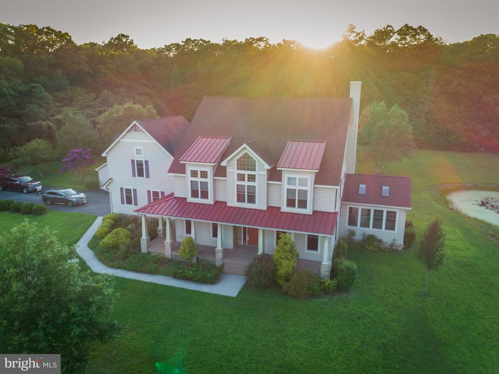 One of a kind property, this unique home stands unparalleled for its beauty, quality, finish, and location with 5.41 acres of land with private backyard built in 2007.  Designed and constructed by a well known builder for his own family. Offers easy access to shopping and the beach. Just ten minutes away from Ocean city, Maryland! Private quarter mile driveway welcomes you home offers unparalleled privacy. You will feel cheerful and serene at this newly renovated home with plenty of natural light with breathtaking high ceilings. Open concept two story living room with elegant ceiling provides spectacular views of the expansive backyard. Remote controlled window blinds allow the right amount of sunlight into your home.Relax in the sunroom which features skylight with heated floors and one of three fireplaces in the home with gorgeous view of the pond. Kitchen has a Viking gas stovetop, built in Microwave, recently installed LG dishwasher. Double oven with built in wine rack above. Walk in pantry is located between dining room and kitchen. Geothermal HVAC and six ultra quiet fans conveniently located throughout the house allows comfort and energy saving. Central vacuum allows easy cleaning in all the rooms. Mudroom allows easy access to the garage, kitchen and the back yard and features a second refrigerator, cabinets and a sink. Outdoor shower right outside the mud room allows the family to wash off the sand easily from day trips to the beach.  A large backyard deck with a hot tub allows large family and friends gatherings and barbecues. The first floor offers beautiful hardwood floors throughout. The living room features floor to ceiling stone wall wood burning fireplace for cozy nights.  An office offers quiet space for study and a view of the pond. The second floor has three bedrooms and two full baths. Along with a loft with attached balcony overlooking the backyard. Recently purchased Samsung washer and dryer is in the enclosed alcove and alongside a built in ir
