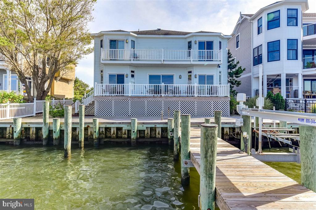 Location!  Location! Location!!!  Stunning DIRECT BAYFRONT living with breathtaking open bay views.  This 6BR/4BA Direct Bayfront single family home is 3343 sq ft.  Homes with unobstructed views of the Bay are rarely available for sale in Heron Harbour Isle.  This beautiful home overlooks the Bay and comes complete with a boat slip with lift, jet ski lift, and an additional single slip right out your back door!!   Share precious family time watching magnificent sunsets from the family room and dining area overlooking the Bay.  You will enjoy your front row seat for the fireworks from Northside Park.  The comfortable dining area is perfect for entertaining family and friends.  The large kitchen has plenty of cabinet space, large countertop and an eat in breakfast area.  There are 2 bedrooms and 2 full baths on the first floor.  On the 2nd floor there are 4 additional bedrooms and 2 full baths.  Two of the bedrooms are Bay facing opening to a deck.  There is a large garage and the driveway affords plenty of parking. This home has brought much joy to the two families that own the home now. They have made priceless memories to last a lifetime.  One of the many highlights of this home is the awesome decks and balconies.  Use them to relax, listen to the water, watch sunsets night after night, and enjoy the boats as they go by.  Imagine yourself in this beautiful home in one of the nicest communities in Ocean City.  Heron Harbour Isle is amenity rich with two outdoor pools, an indoor pool, a kiddie pool, fitness center, social room, sauna, locker room, two Har-Tru tennis courts, sidewalks and piers.  Enjoy your boat, fishing, crabbing, kayaking and paddle boarding all directly out your back door.  The home is being sold fully furnished for your immediate enjoyment.